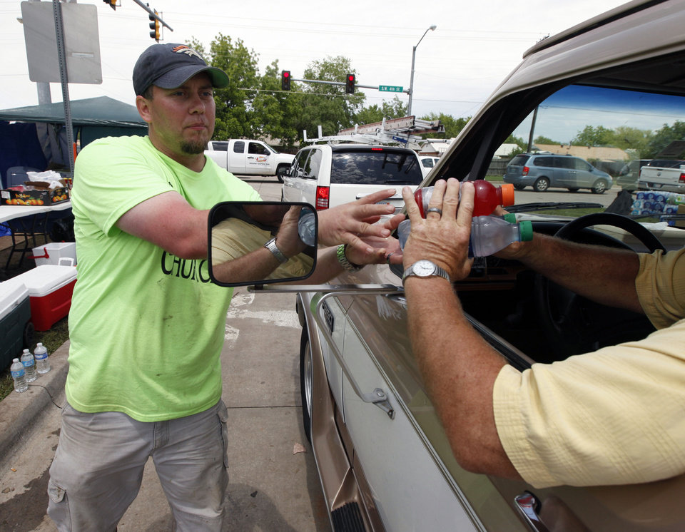 Photo - Mark Wood, from Lawton, gives and receives donated goods on the north perimeter of the tornado devastated part of Moore, OK, Thursday, May 23, 2013,  Photo by Paul Hellstern, The Oklahoman