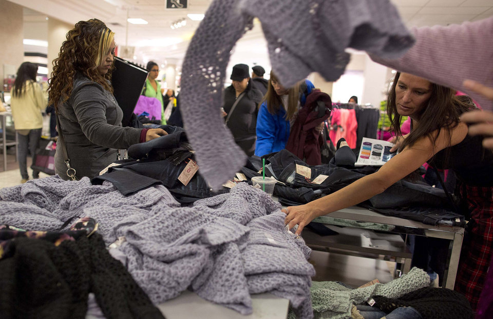 Photo -   Shoppers rummage through a pile of sweaters on sale at a J.C. Penney store, Friday, Nov. 23, 2012, in Las Vegas. Despite a surge of resistance as the sales drew near, with scolding editorials and protests by retail employees and reminders of frantic tramplings past, Black Friday's grip on America may be stronger than ever. (AP Photo/Julie Jacobson)
