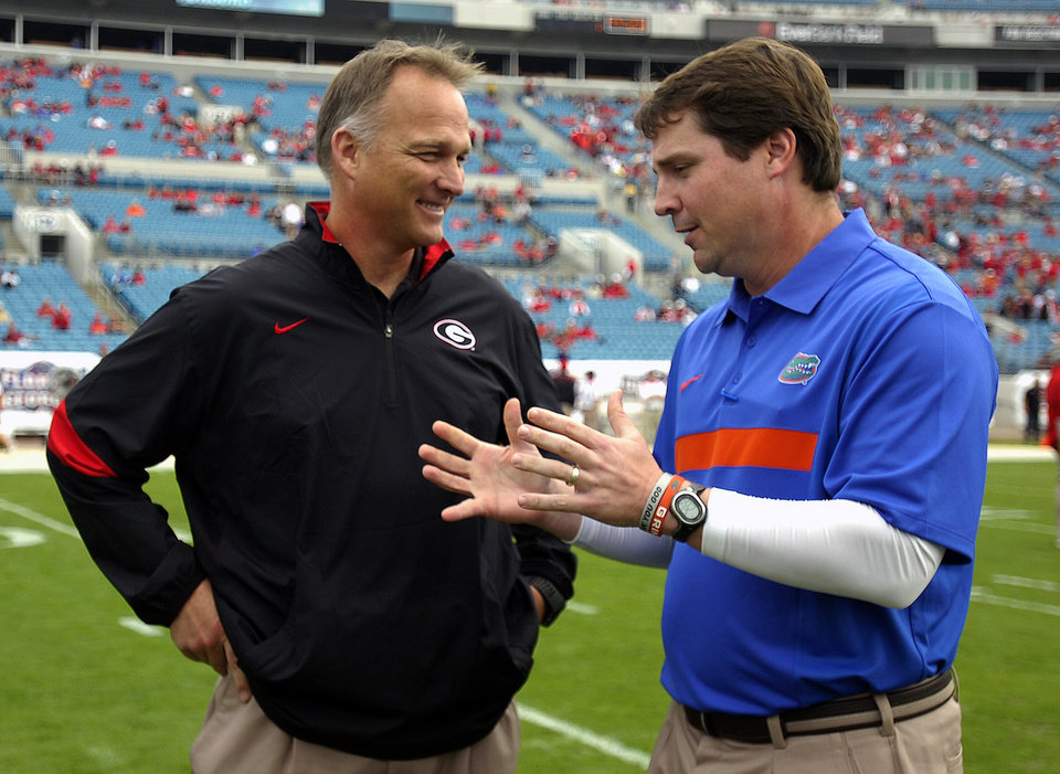Photo -   FILE - In this Oct. 29, 2011, file photo, Florida head coach Will Muschamp, right, and Georgia head coach Mark Richt talk before their NCAA college football game in Jacksonville, Fla. If the No. 12 Bulldogs can beat one decent team _ ONE! _ they will be in line to return to the Southeastern Conference championship game. Of course, it's been a while since they beat a team the caliber of third-ranked Florida. The two schools meet on Saturday in Jacksonville. (AP Photo/Stephen Morton, File)