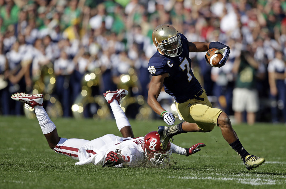 Photo - Notre Dame's TJ Jones (7) is tackled by Oklahoma's Julian Wilson (2) during the first half of an NCAA college football game Saturday, Sept. 28, 2013, in South Bend, Ind. (AP Photo/Darron Cummings)  ORG XMIT: INDC106