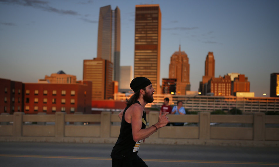 Photo - A run makes his way up Walnut Street during Oklahoma City Memorial Marathon in Oklahoma City, Sunday, April 28, 2019. [Sarah Phipps/The Oklahoman]