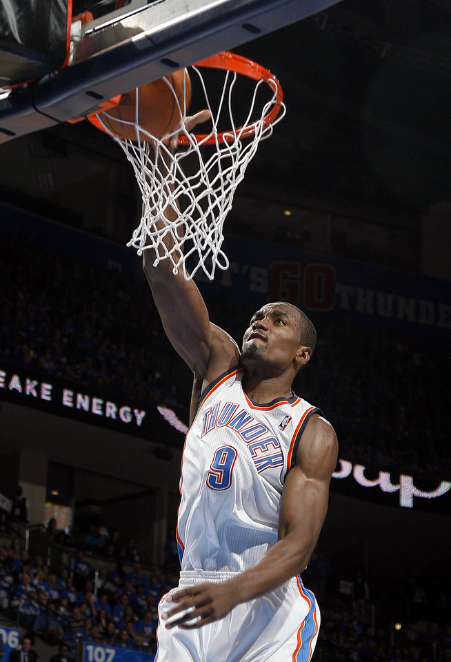 Photo - Oklahoma City's Serge Ibaka (9) dunks the ball during game one of the first round in the NBA playoffs between the Oklahoma City Thunder and the Dallas Mavericks at Chesapeake Energy Arena in Oklahoma City, Saturday, April 28, 2012. Photo by Sarah Phipps, The Oklahoman