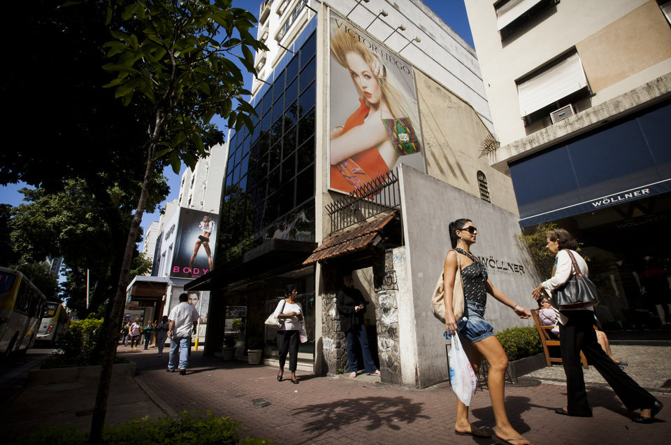 Photo -   Pedestrians walk past giant billboards advertising clothing in Rio de Janeiro, Brazil, Wednesday, May 2, 2012. Billboards on beachfront buildings, advertising along roadways and soccer fields, will now be torn down under the