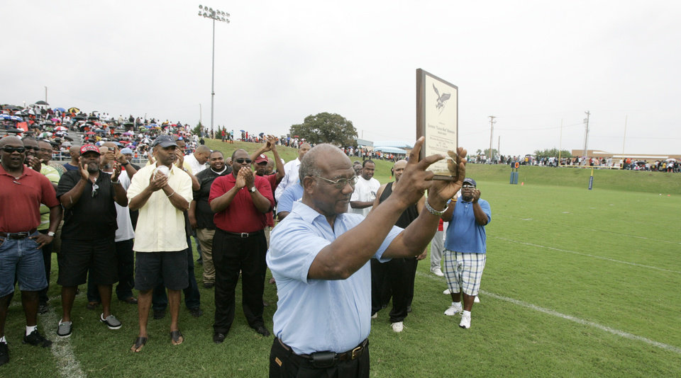 Photo - HIGH SCHOOL FOOTBALL / NAME: Former Millwood head coach Leodies Robinson holds a plaque during a halftime ceremony naming the football field after the legendary coach at Millwood High school in Oklahoma City, Oklahoma September 12, 2009. Photo by Steve Gooch, The Oklahoman ORG XMIT: KOD