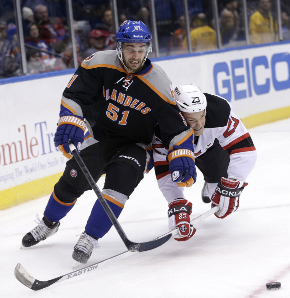 New York Islanders' Frans Nielsen, left, and New Jersey Devils' David Clarkson battle for the puck during the first period of the NHL hockey game on Sunday, Feb. 3, 2013, in Uniondale, N.Y. (AP Photo/Seth Wenig)