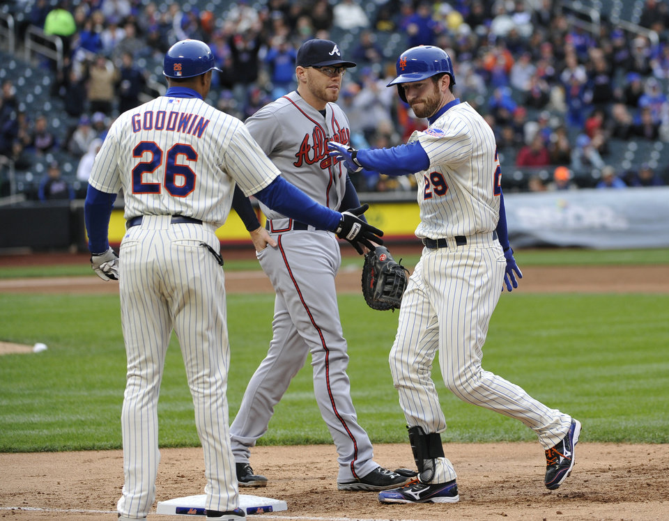 New York Mets' Ike Davis (29) celebrates his single off Atlanta Braves relief pitcher Craig Kimbrel with first base coach Tom Goodwin (26) as Braves first baseman Freddie Freeman watches in the tenth inning of a baseball game that was suspended from Friday night at Citi Field, Saturday, May 25, 2013 in New York. The Braves won 7-5. (AP Photo/Kathy Kmonicek)