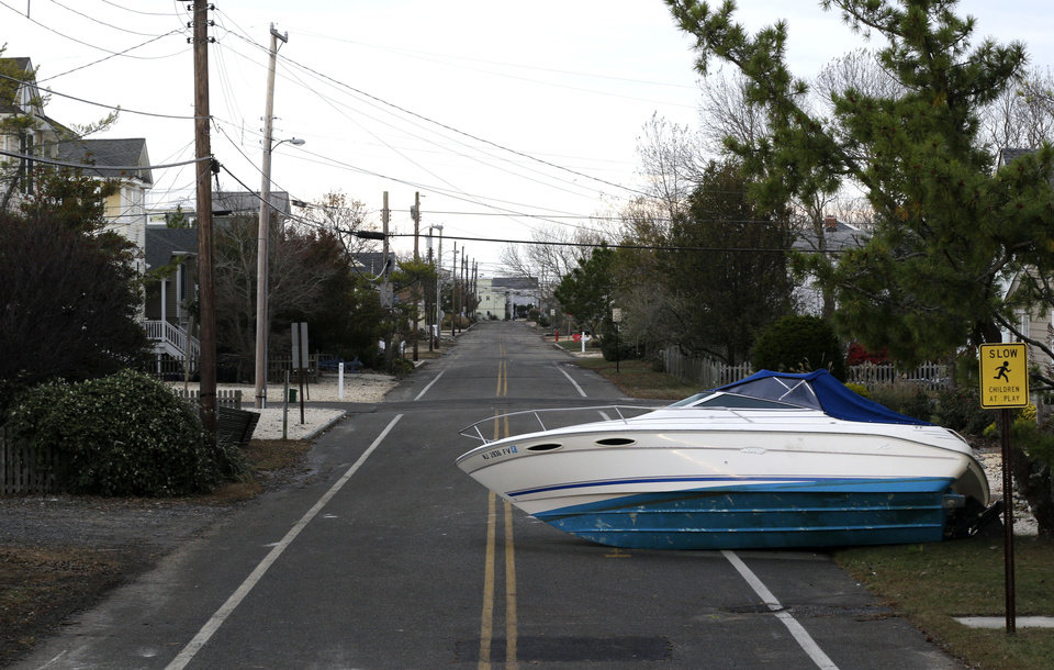 A boat that was carried by surge from Superstorm Sandy sits on a deserted street on Long Beach Island, N.J., Friday, Nov. 2, 2012. Sandy, the storm that made landfall Monday, caused multiple fatalities, halted mass transit and cut power to more than 6 million homes and businesses. (AP Photo/Patrick Semansky) ORG XMIT: NJPS112