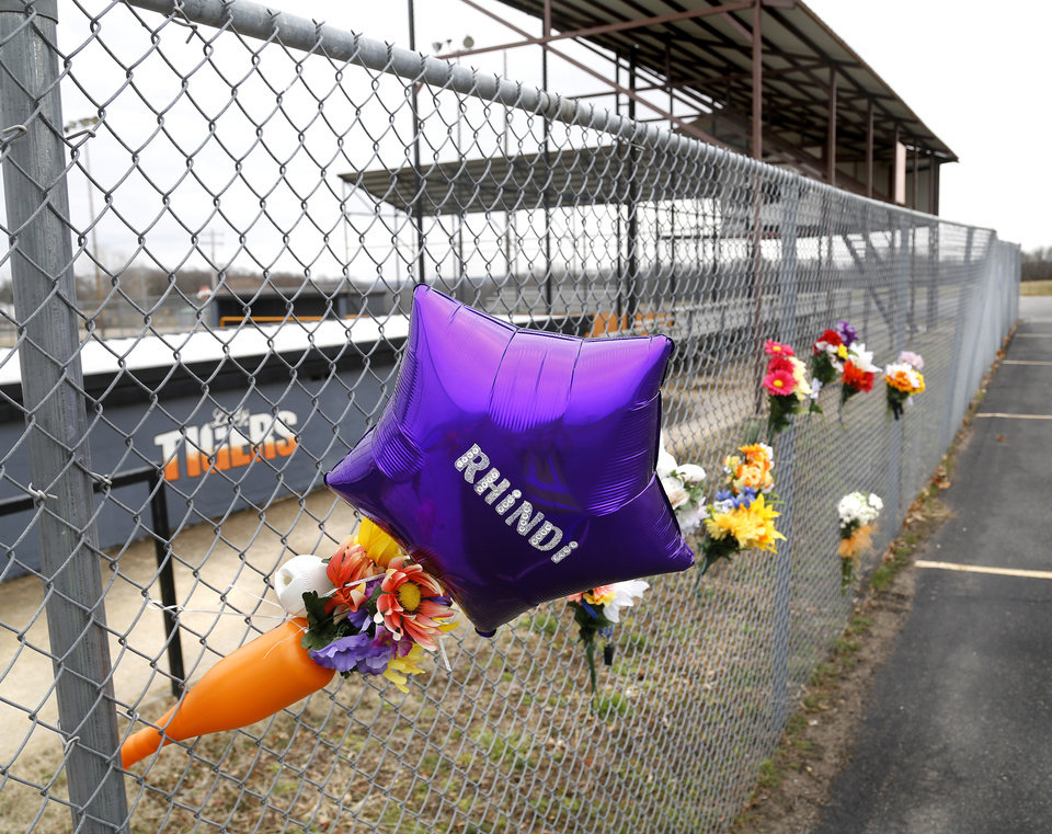 Photo - Flowers, balloons and personalized notes are placed on a chain-link fence near the home dugout of the Konawa softball stadium. Konawa Middle School athlete Rhindi Kay Isaacs, 12, was among three people who died in a fiery, head-on collision Friday evening. The Konawa Public School District said six students from the  junior high school girls softball team were aboard the bus  traveling home at the time of the crash. The team's coach was driving the bus when it was struck by an SUV on SH 377, between Bowlegs and Konawa, in Seminole County. The Oklahoma Highway Patrol said the SUV was traveling in the northbound lane just after 7 p.m. when it swerved and collided with a Konawa School activity bus after the driver of the SUV swerved when passing another vehicle, 