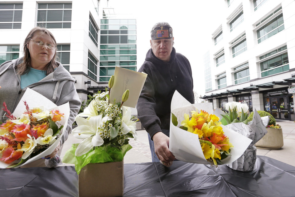 Photo - Cindy Quiring, left, and her husband Roger place flowers at a memorial outside Fisher Plaza, home to KOMO-TV, following a helicopter crash outside the building earlier Tuesday, March 18, 2014, in Seattle. The news helicopter crashed into a city street near Seattle's Space Needle, killing two people and critically injuring a person in a car on the ground.  (AP Photo/Elaine Thompson)