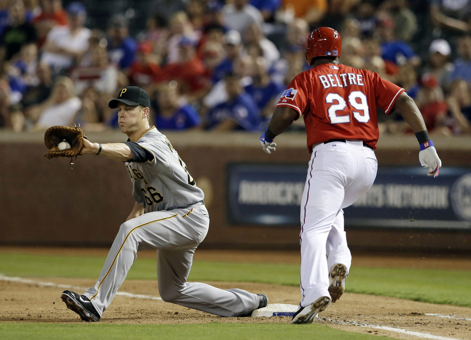 Photo - Pittsburgh Pirates first baseman Justin Morneau reaches out to grab the throw from third on a ground out by Texas Rangers' Adrian Beltre (29) in the fourth inning of a baseball game, Monday, Sept. 9, 2013, in Arlington, Texas. (AP Photo/Tony Gutierrez)