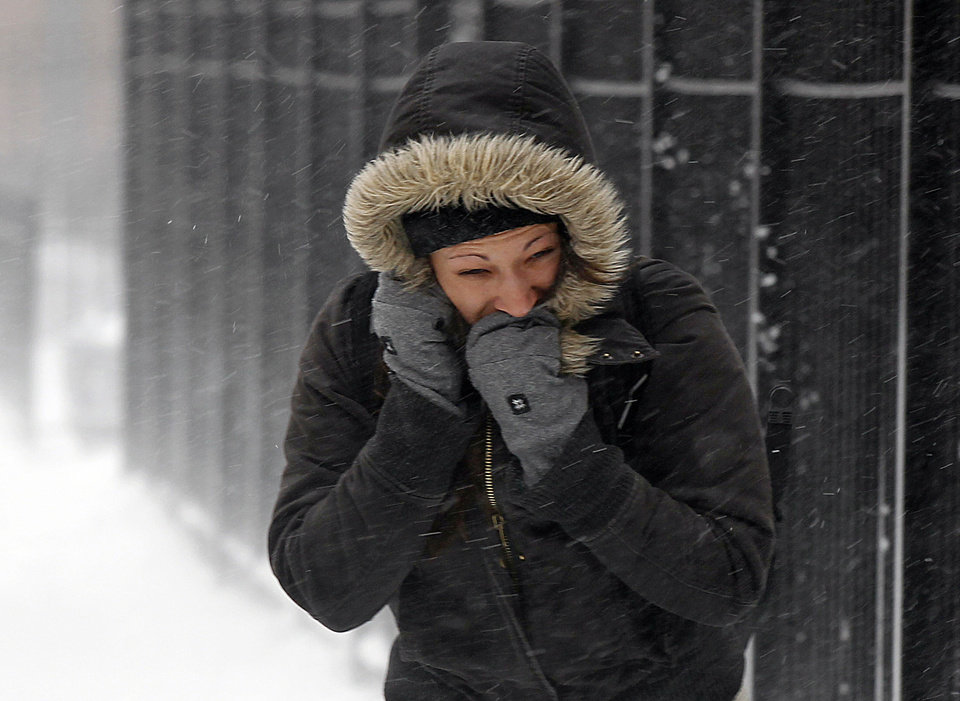 Photo - A commuter walks against blowing snow Wednesday, Feb. 5, 2014, in Chicago. Heavy, blowing snow is moving across much of Illinois as the state gets pelted by the latest round of winter weather. (AP Photo/Kiichiro Sato)