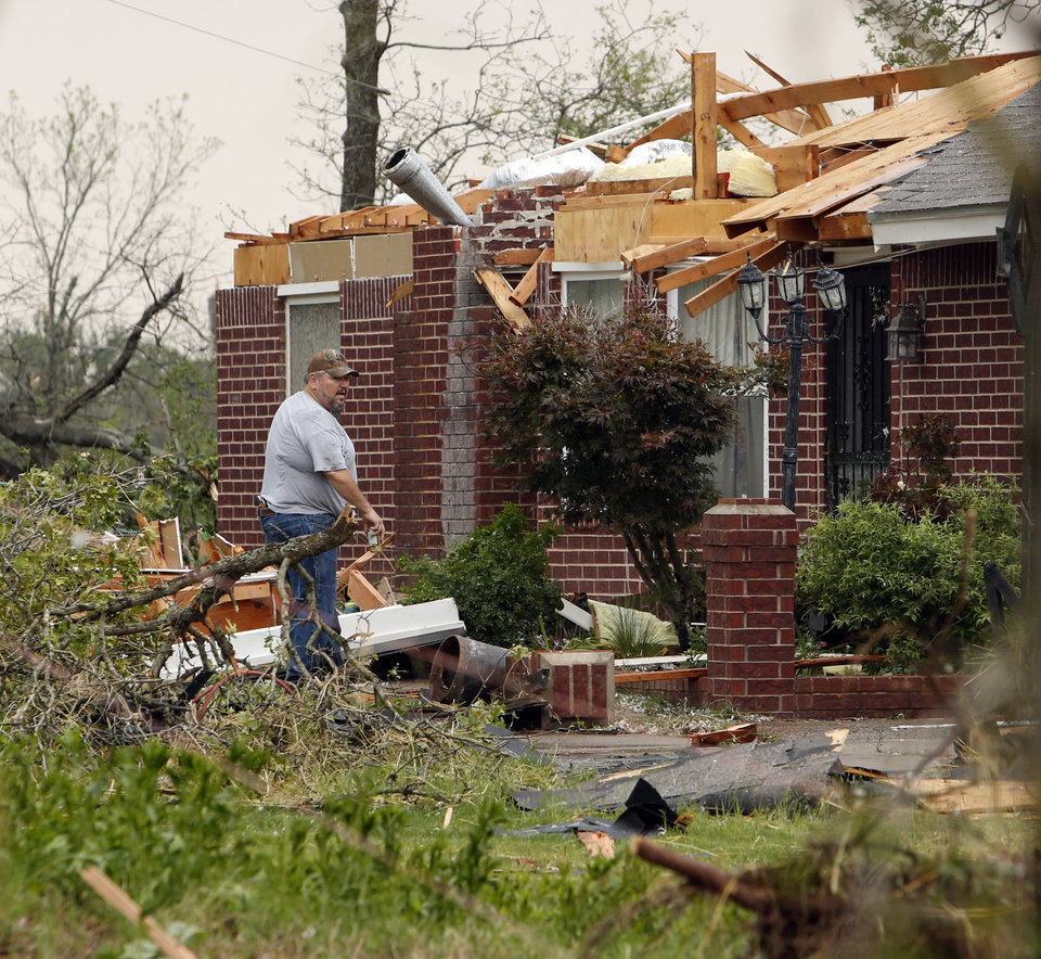Photo - A homeowner looks at damage from a tornado that struck near 156th street and Franklin Road on Sunday, May 19, 2013  in Norman, Okla. Photo by Steve Sisney, The Oklahoman