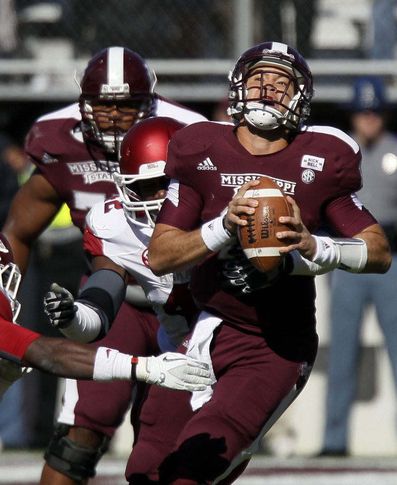 Photo -   Mississippi State quarterback Tyler Russell (17) is sacked from behind by Arkansas defensive end Chris Smith in the first quarter of an NCAA college football game in Starkville, Miss., Saturday, Nov. 17, 2012. (AP Photo/Rogelio V. Solis)