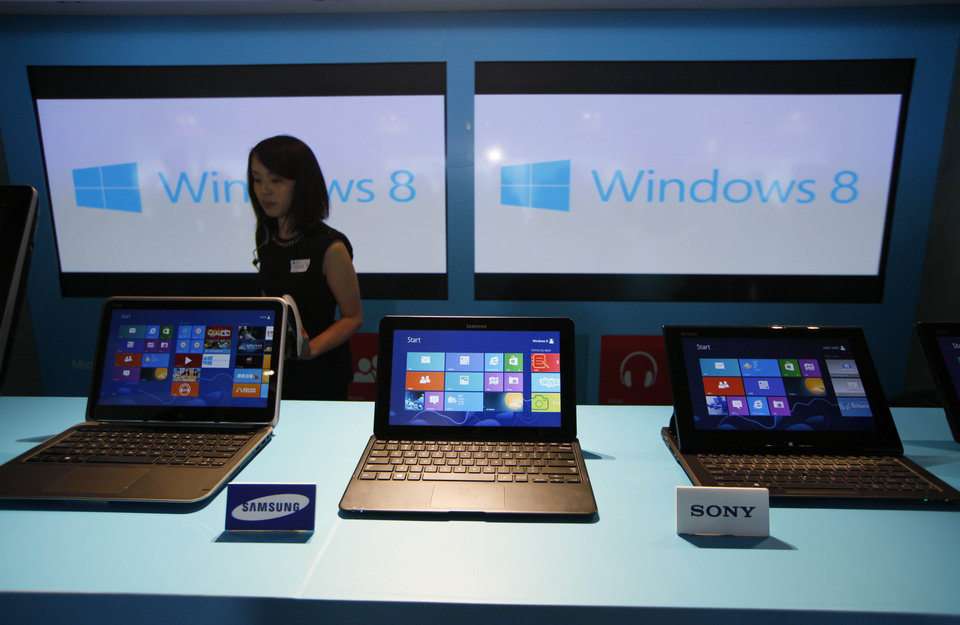 FILE - In this Friday, Oct. 26, 2012, file photo, a woman walks past laptop computers running Microsoft Windows 8 operating system during its launching ceremony in Hong Kong. Research firm IDC says PC global shipments of PCs fell 14 percent in the first three months this year. The appeal of tablets and smartphones is pulling money away from PC sales, but it also blames Microsoft\'s latest version of Windows, which forces users to learn new ways to control their machines. (AP Photo/Kin Cheung, File)