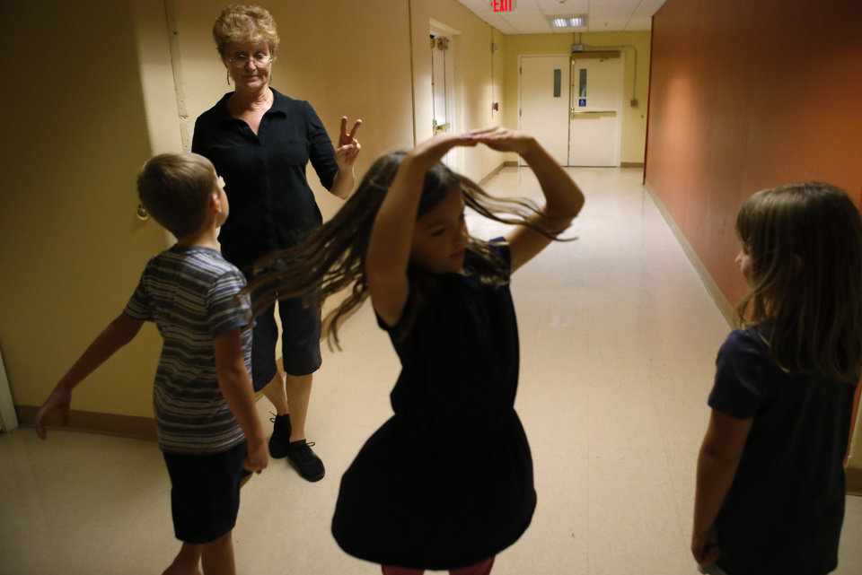 Photo -  Jean Hill works with Evan Goodson, 7, left, Piper Zuniga, 8, and Eleanor Young, 7, during an Irish dance class. [Photo by Bryan Terry, The Oklahoman]