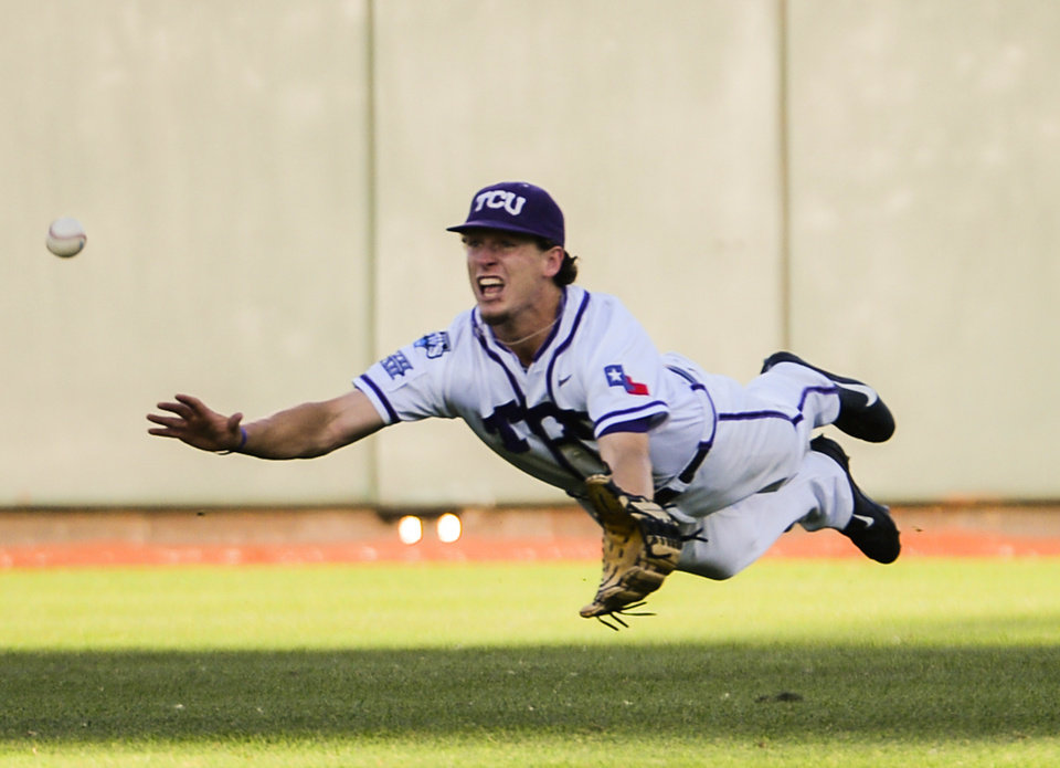 Photo - TCU Center fielder Cody Jones dives for and misses a ball hit for a double by Mississippi's J.B. Woodman in the third inning of an NCAA baseball College World Series elimination game in Omaha, Neb., Thursday, June 19, 2014. (AP Photo/Ted Kirk)