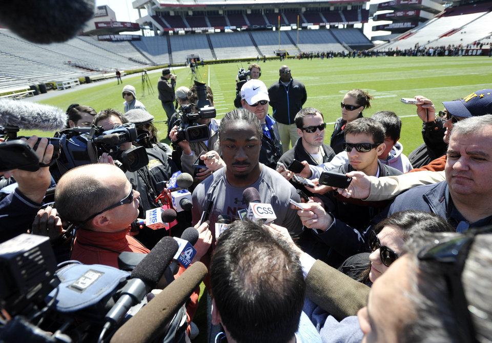 Photo - Running back Marcus Lattimore, center, speaks with the media during South Carolina's NFL football pro day on Wednesday, March 27, 2013, in Columbia, S.C. (AP Photo/Rainier Ehrhardt)