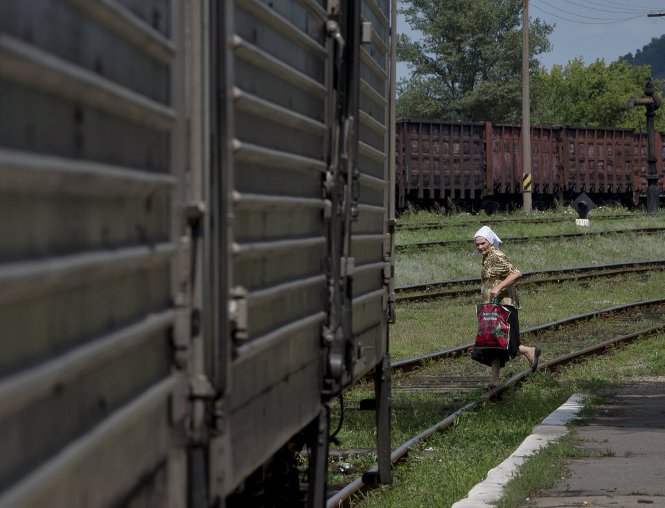 Photo - A woman looks at a refrigerated train loaded with the bodies of victims, in Torez, eastern Ukraine, 15 kilometers (9 miles) from  the crash site of Malaysia Airlines Flight 17, Sunday, July 20, 2014. Armed rebels forced emergency workers to hand over all 196 bodies recovered from the Malaysia Airlines crash site and had them loaded Sunday onto refrigerated train cars bound for a rebel-held city, Ukrainian officials and monitors said. (AP Photo/Vadim Ghirda)