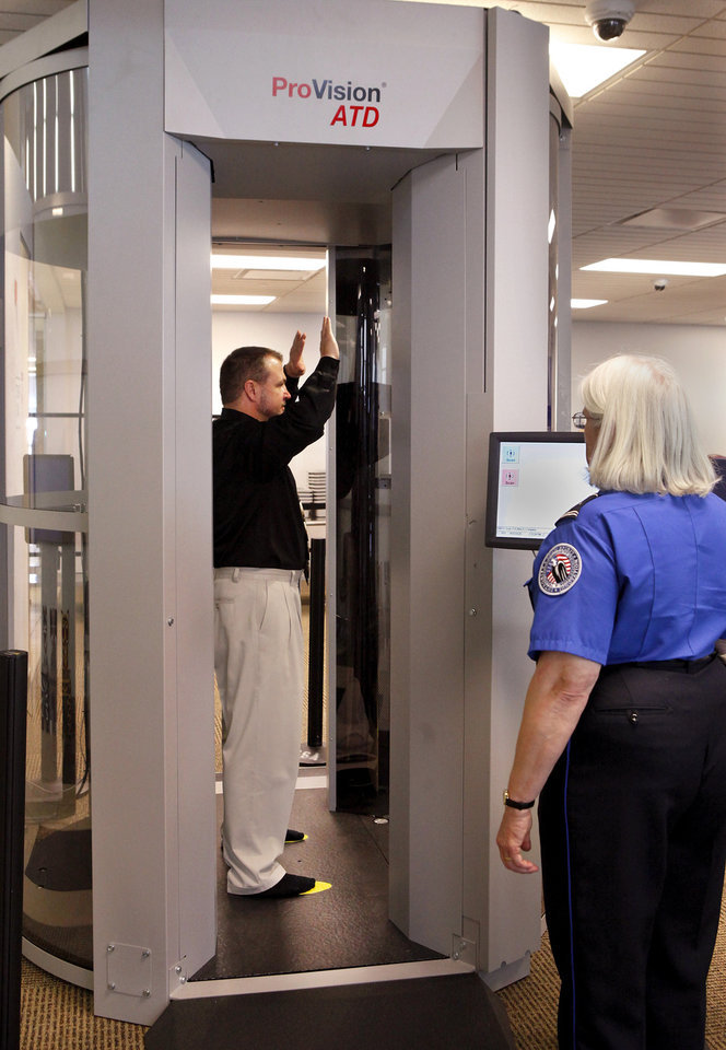 Dennis Malanca, Jr. strikes the required pose for scanning during a demonstration of of the new whole body scanners in the security area between the ticket counters and the passenger boarding gates at Will Rogers World Airport on Wednesday, March 7, 2012. Operating the scanner is Denise Dougherty with TSA. The scanners use millimeter wave technology to detect potential threats. Photo by Jim Beckel, The Oklahoman