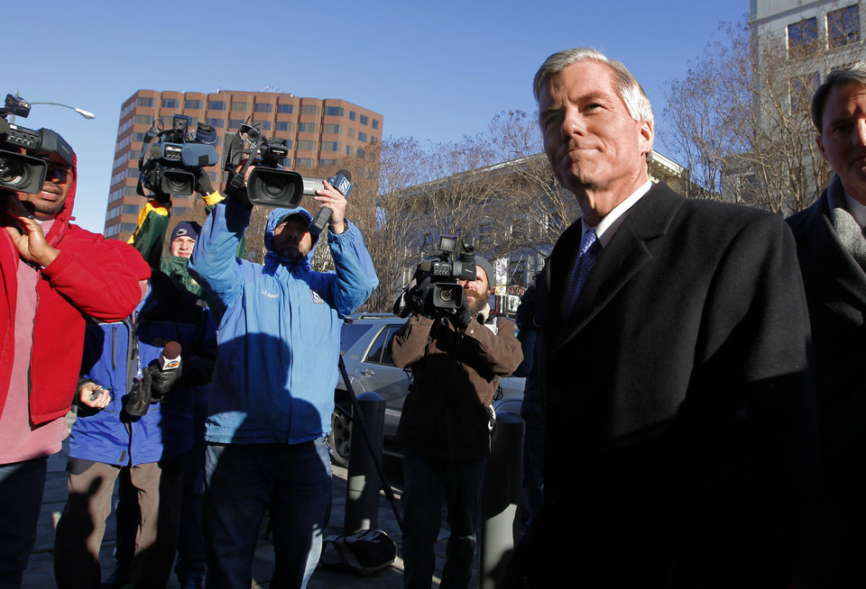 Photo - Former Va. Governor Bob McDonnell, right, surrounded by news cameras, enters U.S. District Court in Richmond, Va. for his and his wife Maureen's bond hearing and arraignment on Friday, Jan. 24, 2014 on federal corruption charges. The McDonnells, flanked by their children, did not comment as they entered the courthouse. (AP Photo/ Richmond Times-Dispatch, Dean Hoffmeyer)