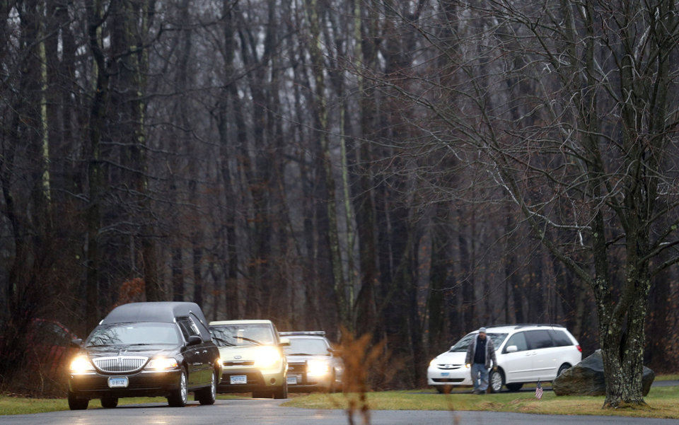 Photo - A hearse arrives at B'nai Israel Cemetery with the body of Noah Pozner, a six-year-old killed in an elementary school shooting, during funeral services, Monday, Dec. 17, 2012, in Monroe, Conn. Authorities say gunman Adam Lanza killed his mother at their home on Friday and then opened fire inside the Sandy Hook Elementary School in Newtown, killing 26 people, including 20 children, before taking his own life. (AP Photo/Julio Cortez) ORG XMIT: CTJC124
