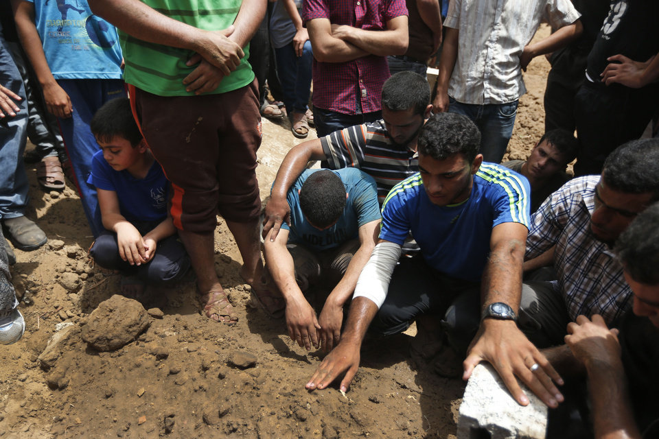 Photo - Palestinians mourn over the grave of a member of the al-Batsh family who were killed in Saturday's Israeli airstrike, during a funeral procession in Gaza City on Sunday, July 13, 2014. The strike hit the home of Gaza police chief Taysir al-Batsh and damaged a nearby mosque as evening prayers ended Saturday, killing at least 18 people, wounding 50 and leaving some people believed to be trapped under the rubble, said Palestinian Health Ministry official Ashraf al-Kidra. (AP Photo/Lefteris Pitarakis)