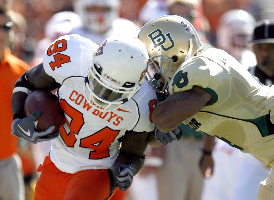 Photo - OSU's Hubert Anyiam (84) is pushed out of bounds by Baylor's Jeremy Williams (4)during the college football game between Baylor University and Oklahoma State University (OSU) at Floyd Casey Stadium in Waco, Texas, Saturday, Oct. 24, 2009.  Photo by Sarah Phipps, The Oklahoman