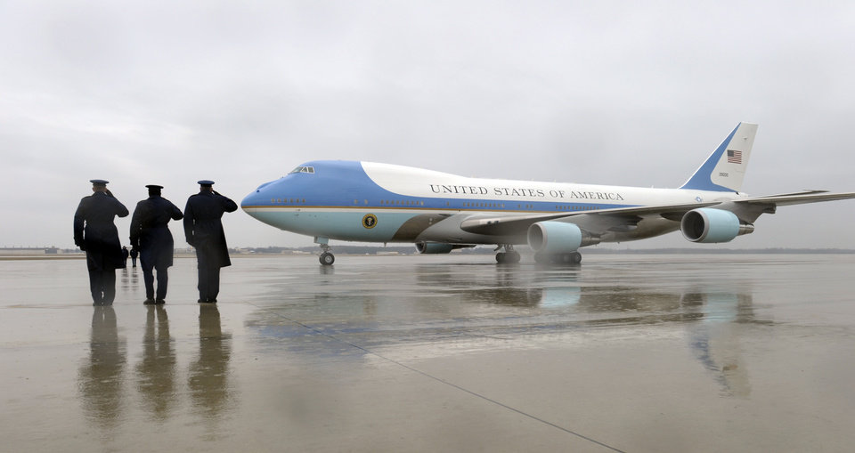 Air Force personnel salute as Air Force One, with President Barack Obama on board, arrives at in the rain at Andrews Air Force Base, Md., Tuesday, Feb. 26, 2013. The president was returning from Newport News, Va., for an event on the automatic budget cuts. (AP Photo/Susan Walsh)