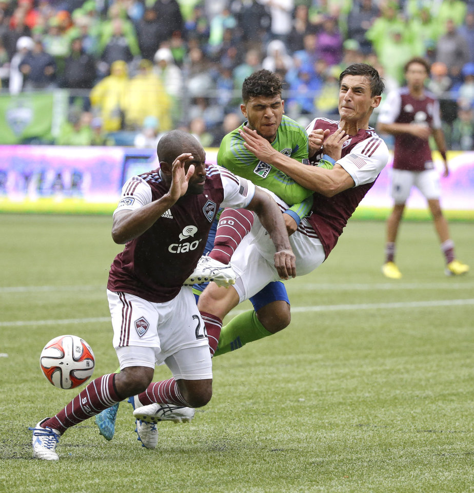 Photo - Seattle Sounders' DeAndre Yedlin, center, collides with Colorado Rapids' Thomas Piermayr, right, as the ball gets kicked past Colorado Rapids's Marvell Wynne, left, in the second half of an MLS soccer match, Saturday, Aug. 30, 2014, in Seattle. The Sounders defeated the Rapids, 1-0. (AP Photo/Ted S. Warren)