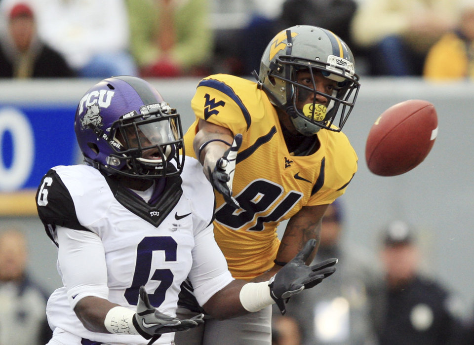 Photo -   West Virginia wide receiver J.D. Woods (81) catches a touchdown pass in front of TCU safety Elisha Olabode (6) during the first half of their NCAA college football game in Morgantown, W.Va., on Saturday, Nov. 3, 2012. (AP Photo/Christopher Jackson)