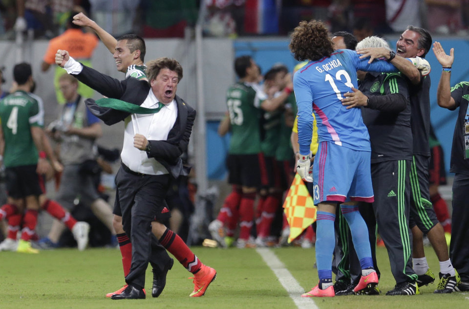 Photo - In this June 23, 2014 photo, Mexico's head coach Miguel Herrera celebrates after Mexico's Andres Guardado  scored his side's second goal during the group A World Cup soccer match between Croatia and Mexico at the Arena Pernambuco in Recife, Brazil. Mexico's national soccer coach just can't keep his joy bottled up, and his enthusiasm has made him one of the most entertaining and popular figures of the World Cup and an Internet sensation worldwide. (AP Photo/Petr David Josek)