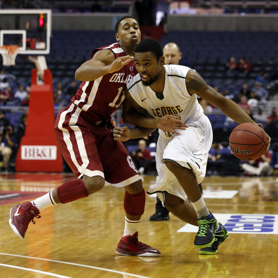 Photo - George Mason guard Sherrod Wright (10) tries to get past Oklahoma guard Isaiah Cousins (11) during the second half of an NCAA college basketball game in the BB&T Classic, Sunday, Dec. 8, 2013, in Washington. Oklahoma won 81-66. (AP Photo/Alex Brandon)