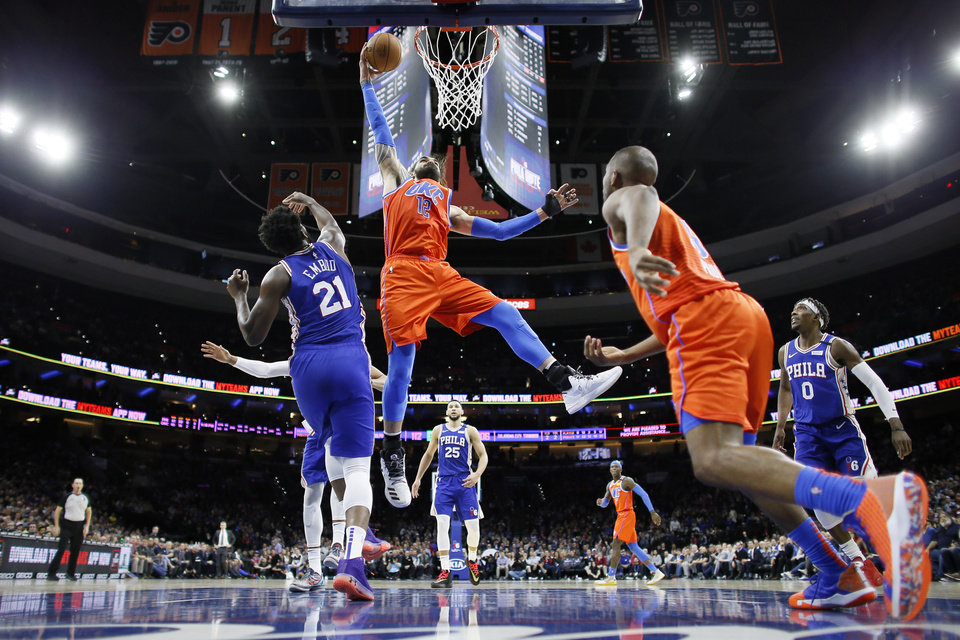 Photo - Oklahoma City Thunder's Steven Adams (12) goes up to dunk past Philadelphia 76ers' Joel Embiid (21) during the second half of an NBA basketball game, Monday, Jan. 6, 2020, in Philadelphia. (AP Photo/Matt Slocum)