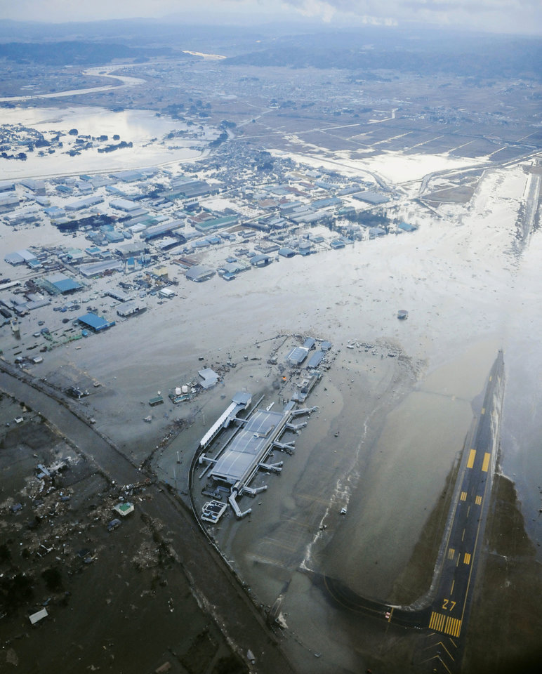 Photo - Tarmac and surrounding area are covered with water from tsunami at Sendai Airport in Sendai, Miyagi Prefecture (state) after Japan was struck by a strong earthquake off its northeastern coast Friday, March 11, 2011. (AP Photo/Kyodo News) JAPAN OUT, MANDATORY CREDIT, FOR COMMERCIAL USE ONLY IN NORTH AMERICA ORG XMIT: TOK831