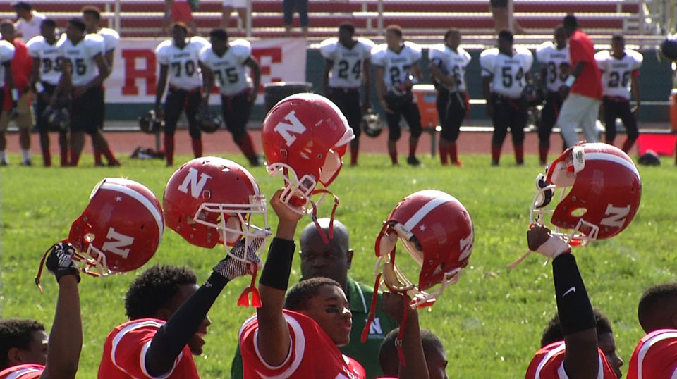 Photo - In this image taken from video on Saturday, Aug. 23, 2014, Normandy High School football players, students and parents observe a moment of silence for Michael Brown before the start of the first game of the school year, in Ferguson, Mo. Brown, 18, was killed by a Ferguson police officer on Aug. 9, eight days after he graduated from the high school. (AP Photo/Alex Sanz)