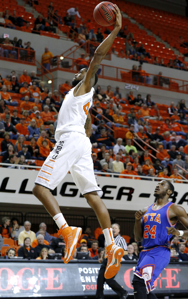 Oklahoma State's Michael Cobbins (20) dunks the ball in front of Texas-Arlington's Kevin Butler (24) during a college basketball game between Oklahoma State University and UT Arlington at Gallagher-Iba Arena in Stillwater, Okla., Wednesday, Dec. 19, 2012. Photo by Bryan Terry, The Oklahoman
