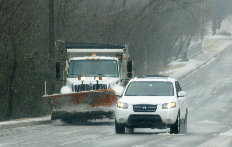 Photo - A motorist passes a sand and salt truck on Coltrane Sunday, December 74, 2015. Photo by Doug Hoke, The Oklahoman