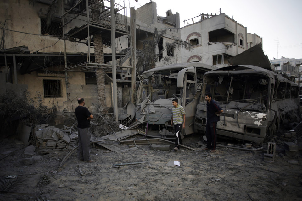 Photo - Palestinians check the damage of their destroyed houses and buses following late night Israeli strikes in Gaza City, Wednesday, Aug. 20, 2014. (AP Photo/Khalil Hamra)