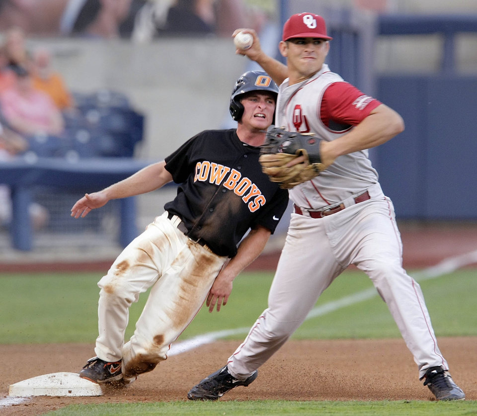 Oklahoma State�s Saulyer Saxon, left, is out at third as Oklahoma third baseman Garrett Carey turns a double play during Friday�s game in Tulsa.  PHOTO BY MICHAEL WYKE, TULSA WORLD