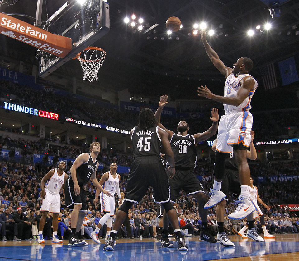 Photo - Oklahoma City's Kendrick Perkins (5) puts up a shot over Brooklyn Nets' Gerald Wallace (45) and Reggie Evans (30) during the NBA basketball game between the Oklahoma City Thunder and the Brooklyn Nets at the Chesapeake Energy Arena on Wednesday, Jan. 2, 2013, in Oklahoma City, Okla. Photo by Chris Landsberger, The Oklahoman