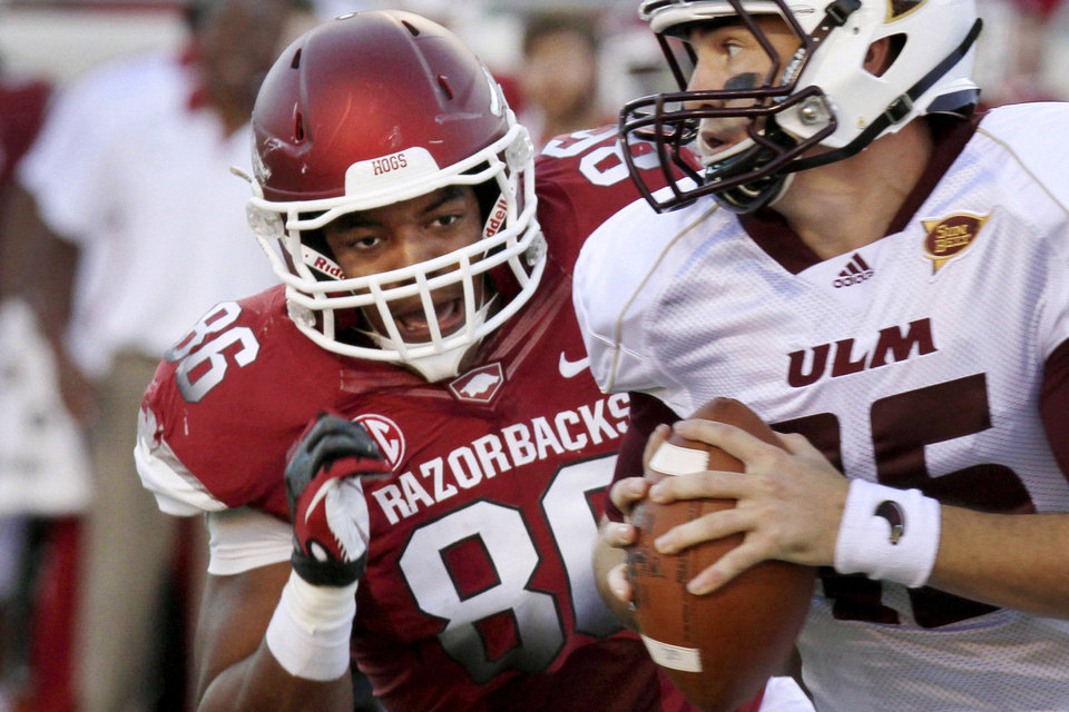 Photo - FILE - In this Sept. 8, 2012, file photo, Arkansas defensive end Trey Flowers, left, pressures Louisiana Monroe quarterback Kolton Browning (15) during an NCAA college football game in Little Rock, Ark. Flowers will return to Arkansas for his senior year after he received a third-round NFL draft grade following last season. (AP Photo/Danny Johnston, File)