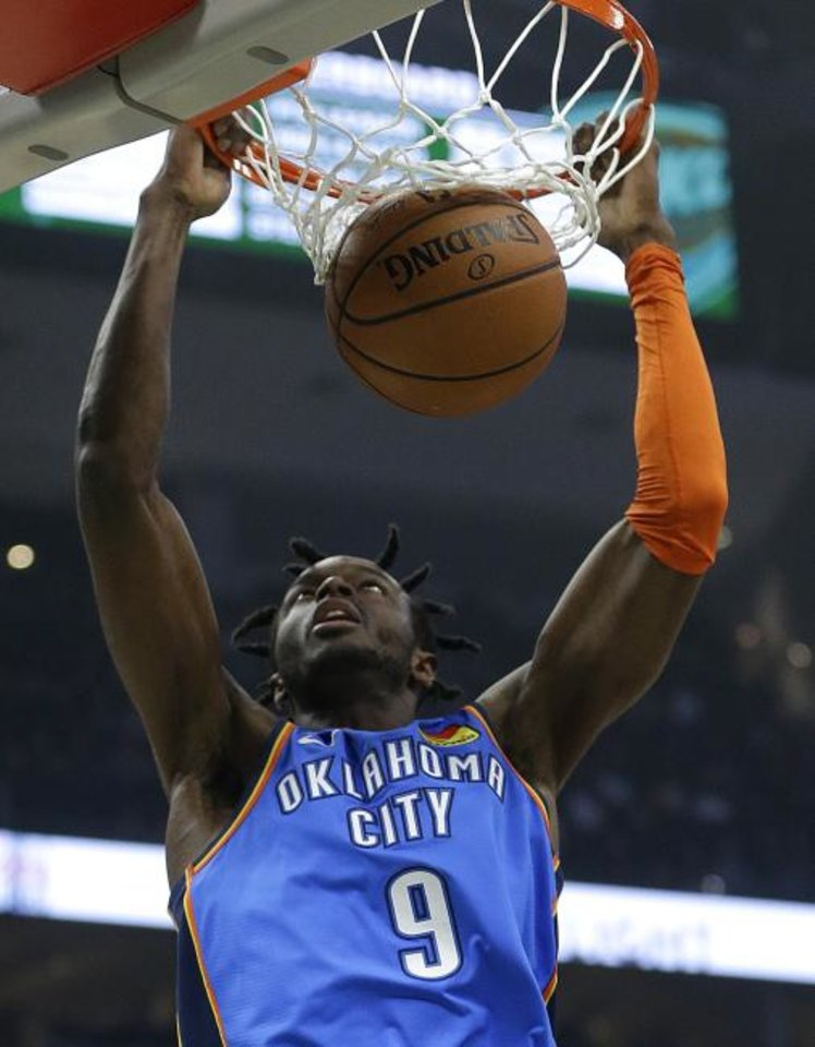 Photo -  Oklahoma City's Jerami Grant dunks during the Thunder's 127-116 victory in Milwaukee Wednesday night which clinched the No. 6 seed in the Western Conference playoffs. [AP Photo/Aaron Gash]