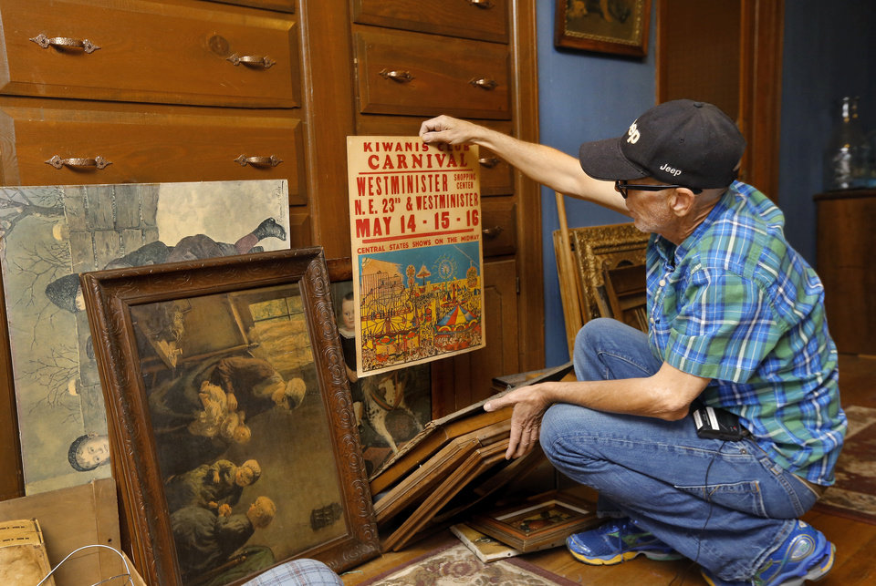 Photo -  Max Hester holds an old promotional poster for a Kiwanis Club carnival in Nicoma Park. Hester has been searching through numerous items piled against a wall in the upstairs hallway of his parents' home in Choctaw. Photo by Jim Beckel, The Oklahoman   Jim Beckel