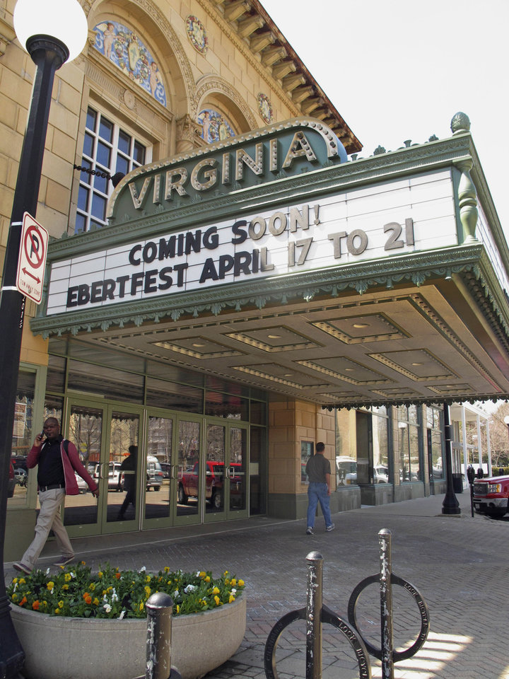 Photo - This April 5, 2013 photo shows people walking past the Virginia Theater in Champaign, Ill., with the marquee announcing the upcoming Ebertfest film festival running April 17-21. Through his television shows, movies reviews and essays, movie critic Roger Ebert belonged to the world beyond nearby Urbana, Ill. One part of Ebert's life that got little attention as the nation mourned his sudden death April 4 was how much he meant to this university town where he grew up. (AP Photo/David Mercer)