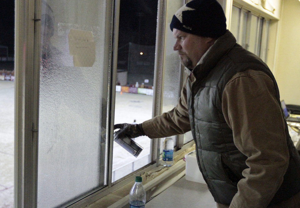 Photo - Blanchard supporter Jason Stratton sprays deicer on press box windows before the game as Newcastle plays Blanchard in Class 3A high school football playoffs on Friday, Nov. 22, 2013, in Blanchard, Okla. Photo by Steve Sisney, The Oklahoman