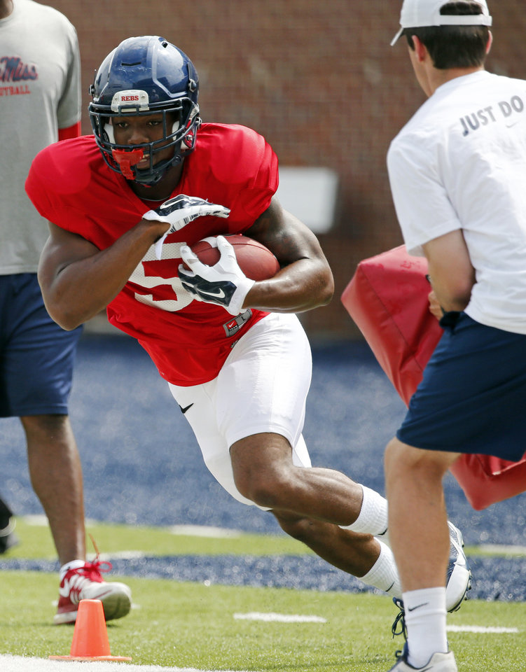 Photo - Mississippi running back I'Tavius Mathers (5) cuts upfield during the team's final open NCAA college football practice, Saturday, Aug. 9, 2014, at Mississippi, in Oxford, Miss. Players were involved in individual and team drills. (AP Photo/Rogelio V. Solis)