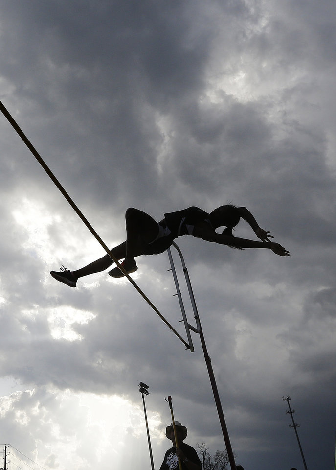 Photo - A high school student pole vaults against threatening skies in Montgomery, Ala., Monday, March 18, 2013. The track meet at Montgomery Academy was canceled as the state long weather front of severe thunderstorms approached. (AP Photo/Dave Martin)
