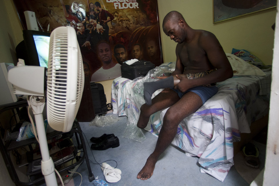 Photo - In this July 20, 2012 photo, professional dancer Georges Exantus prepares to put on his prosthetic limb in his bedroom as he prepares for his wedding in Port-au-Prince, Haiti.  Exantus thought he'd never dance again.  The earthquake three years ago in Haiti's capital flattened the apartment where he was living, where he spent three days trapped under a heap of jagged rubble. After friends dug him out, doctors amputated his right leg just below the knee. Israeli doctors and physical therapists who came to Haiti after the quake sent him to Israel for surgery and rehabilitation. Three years later, the 32-year-old professional dancer is back on the floor, spinning away as he does the salsa, cha-cha and samba. (AP Photo/Dieu Nalio Chery)