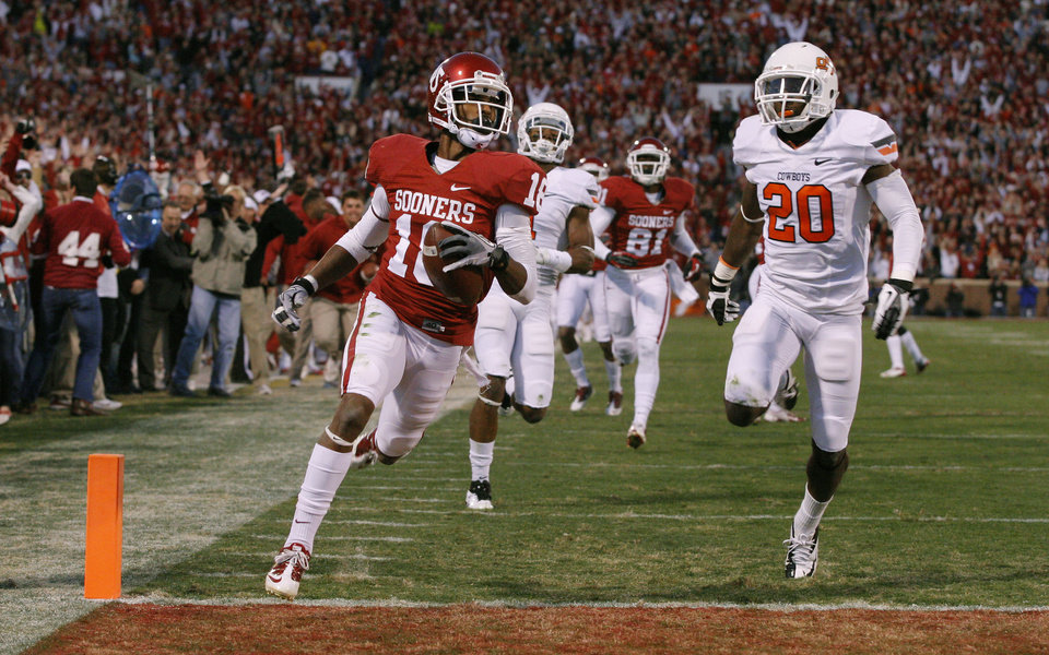 Photo - Oklahoma's Jalen Saunders (18) scores a touchdown past Oklahoma State's Larry Stephens (20) on a punt return during the Bedlam college football game between the University of Oklahoma Sooners (OU) and the Oklahoma State University Cowboys (OSU) at Gaylord Family-Oklahoma Memorial Stadium in Norman, Okla., Saturday, Nov. 24, 2012. Oklahoma won 51-48. Photo by Bryan Terry, The Oklahoman