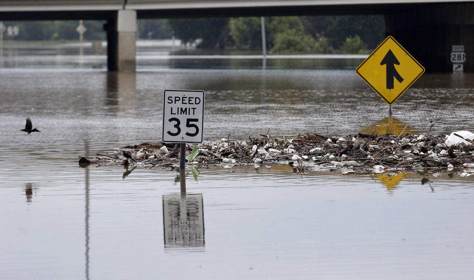Photo - Debris gathers around street signs on a flooded road, Sunday, May 26, 2013, in San Antonio. Heavy rains and flooding are being blamed for at least two deaths in San Antonio. (AP Photo/Eric Gay)